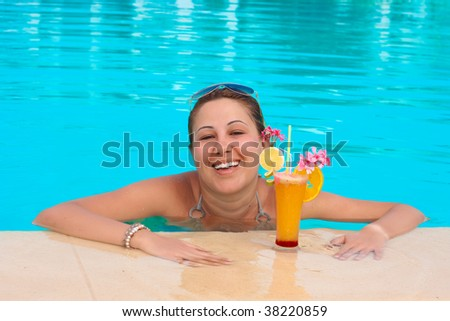 Happiness young woman enjoy in the pool with cocktail.