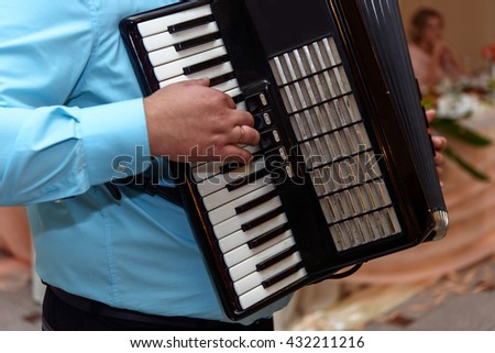 happy accordion musician playing at wedding reception, hand on harmonica