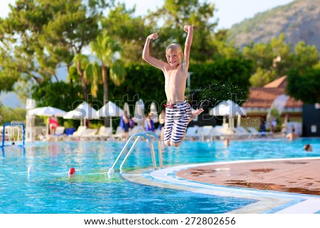 Happy active child, blonde caucasian teenage boy, jumping and diving into swimming pool in tropical resort at sunset - summertime vacation concept - stock photo