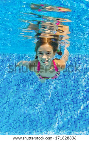 Happy active child swims underwater in pool, beautiful healthy girl swimming and having fun on family summer vacation, kids sport concept, vertical image