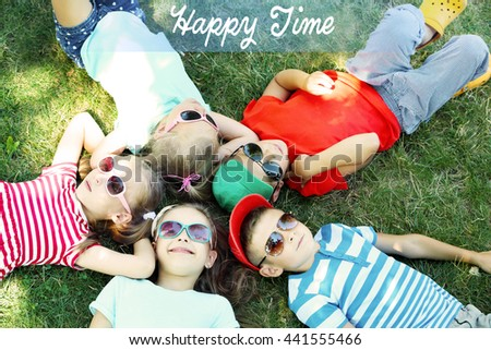 Happy active children lying on green grass in park with text Happy Time - stock photo