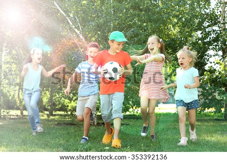 Happy active children playing with football in park - stock photo