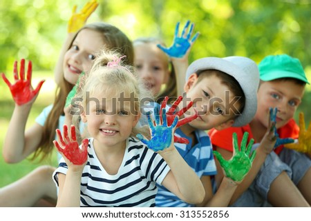 Happy active children with bright colored palms in park