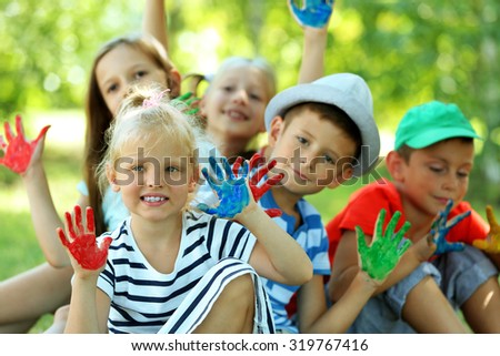 Happy active children with bright colored palms in park - stock photo