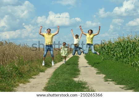 Happy active family jumping on field road - stock photo