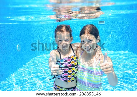 Happy active kids play underwater in swimming pool, girls diving and having fun, children on summer  vacation, sport concept