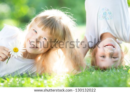 Happy active kids playing on green grass in spring park - stock photo