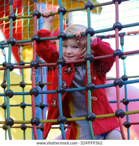 Happy active little child, blonde curly toddler girl wearing beautiful red duffle coat, having fun at playground in the park on sunny autumn day - stock photo