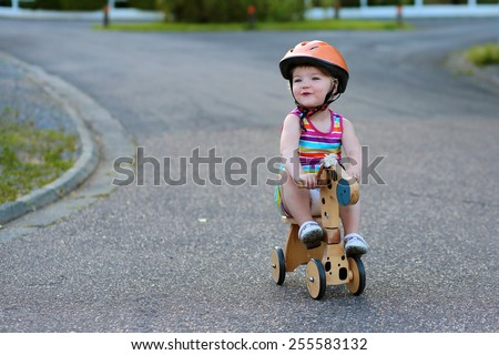 Happy active little kid, beautiful blonde toddler girl in colorful dress and safety helmet playing outdoors on the street riding her push bike, wooden horse with three wheels, on a sunny summer day - stock photo