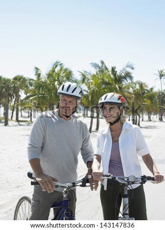 Happy active senior couple with bicycles on tropical beach - stock photo