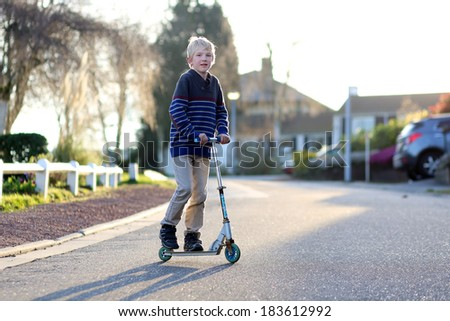 Happy active teenager boy driving with scooter playing on the street on a warm summer evening during sunset - stock photo