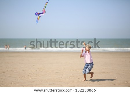 Happy active teenager boy running on a sandy beach at a sea playing with kite on a windy sunny day - stock photo
