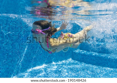 Happy active underwater child swims in pool, beautiful healthy girl swimming and having fun on family summer vacation, kids sport  - stock photo