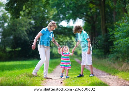 Happy active woman enjoying hiking with two children, school age boy and cute curly toddler girl walking together in a beautiful pine wood forest on a sunny summer day - stock photo