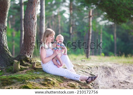 Happy active woman playing with a cute little child, adorable laughing baby boy, having fun together enjoying hiking in a beautiful sunny pine wood forest on a warm summer day - stock photo