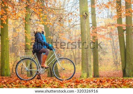 Happy active woman riding bike bicycle in fall autumn park. Glad young girl in jacket and scarf relaxing. Healthy lifestyle and recreation leisure activity. - stock photo