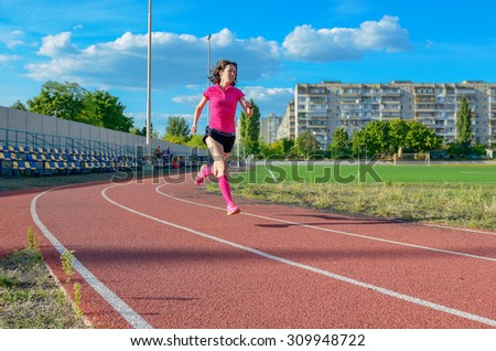 Happy active woman running on track, sprinting and working out on stadium, sport and fitness in city, urban background  - stock photo