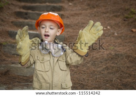 Happy Adorable Child Boy with Big Gloves, Hard Hat and Goggles Playing Handyman Outside. - stock photo