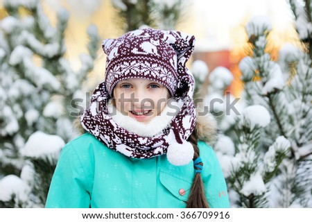 Happy adorable kid girl wearing a colorful jacket  and knitted hat playing in a beautiful snowy winter park on beauty day - stock photo