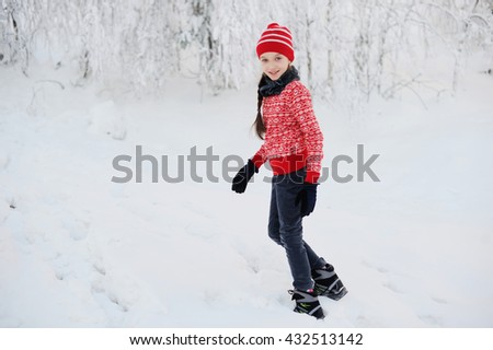 Happy adorable kid girl wearing a colorful red sweater and knitted hat playing in a beautiful snowy winter park on beauty day - stock photo
