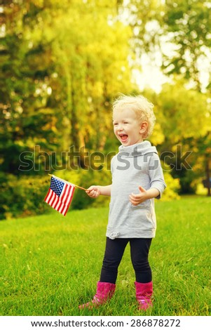 Happy adorable little blond Caucasian girl smiling laughing holding and waving American flag outside  celebrating 4th july,  Independence Day, Flag Day concept. - stock photo