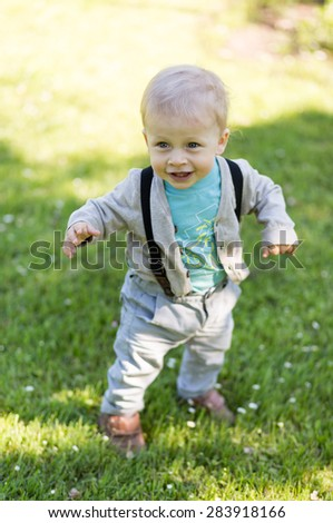 Happy adorable little boy walking in the grass in sunny day.  - stock photo