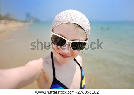 Happy  adorable little girl on summer vacation taking selfie with smartphone - stock photo
