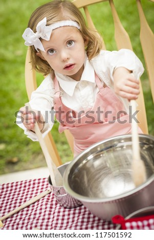 Happy Adorable Little Girl Playing Chef Cooking in Her Pink Outfit. - stock photo