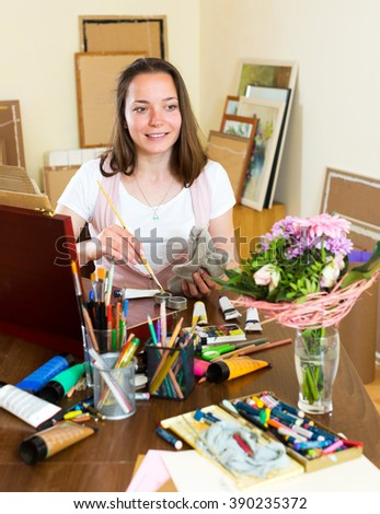 Happy adult artist paints a picture at home - stock photo