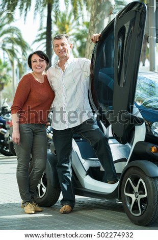 Happy adult couple sitting in twizy electric on city street
