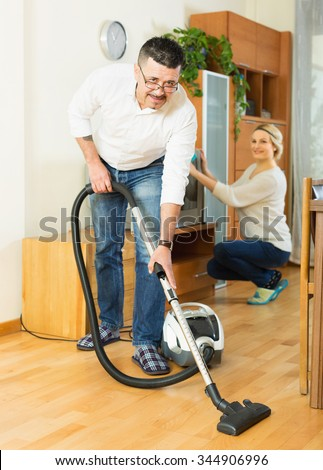 Happy adult spouses dusting and hoovering at domestic interior - stock photo