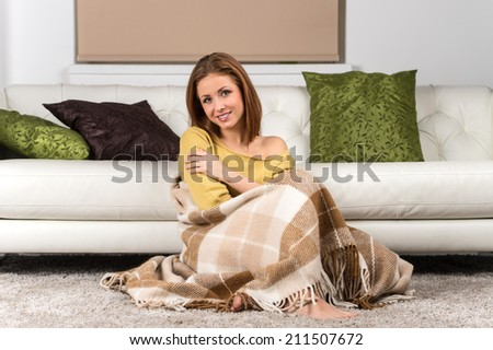 Happy adult woman sitting on her house floor. young girl covered with blanket and smiling  - stock photo