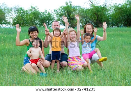 happy adults and children smiling waving hands