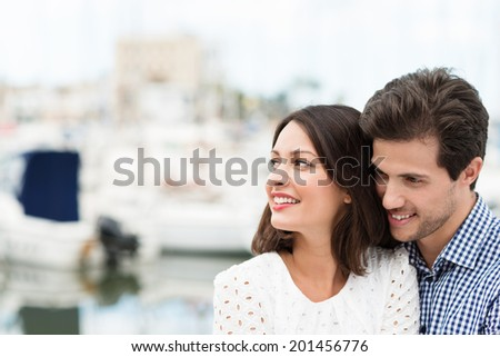 Happy affectionate attractive young couple standing close together looking across the frame to the left, with copyspace - stock photo