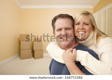 Happy Affectionate Couple in Room of New House With Only Boxes on the Floor. - stock photo