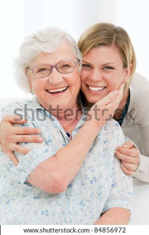 Happy affectionate senior woman embrace her granddaughter at home - stock photo