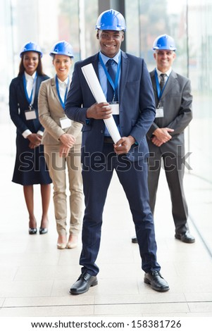 happy african american architect standing in front of colleagues in modern office - stock photo