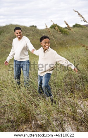 Happy African-American boy pulling father along sand dunes and grass at beach - stock photo