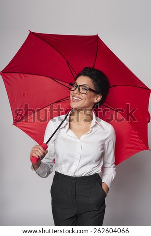 Happy african american business woman standing with red umbrella, over gray background - stock photo