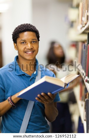 happy african american college boy reading in library - stock photo