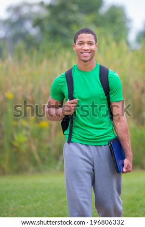 Happy African American College Student Holding Laptop walking outdoor - stock photo