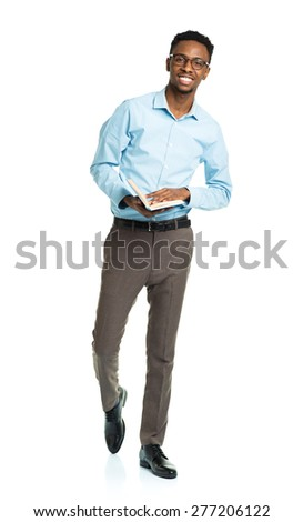 Happy african american college student with book in his hands standing on white background - stock photo