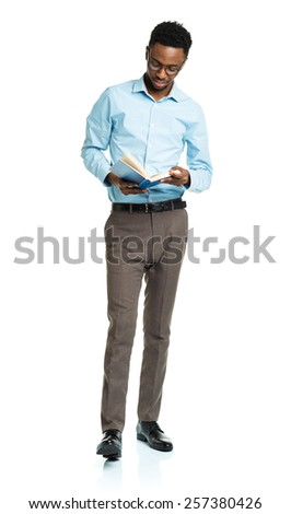 Happy african american college student with books in his hands  standing on white background - stock photo