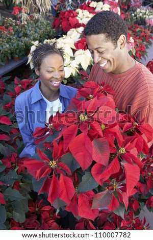 Happy African American couple buying flowers - stock photo