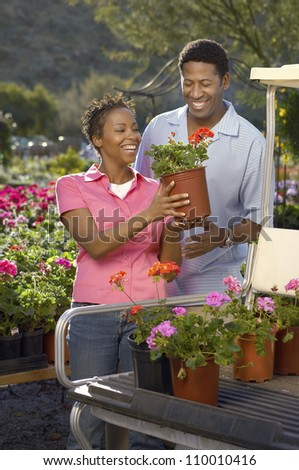 Happy African American couple loading plants on golf cart - stock photo