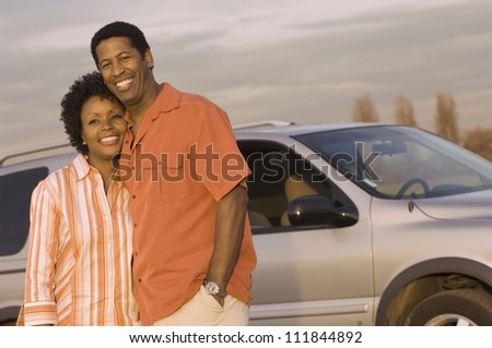 Happy African American couple standing in front a car