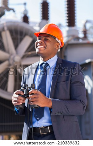 happy african american electrical businessman with binoculars at plant - stock photo