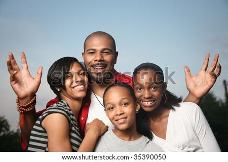 Happy African American family. Father with three teenage daughters together having a good time. - stock photo