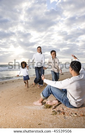 Happy African-American family running to father on beach - stock photo