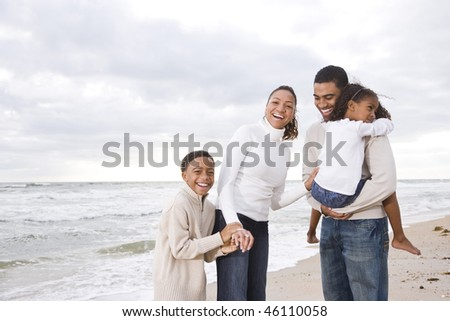 Happy African-American family with two children on beach